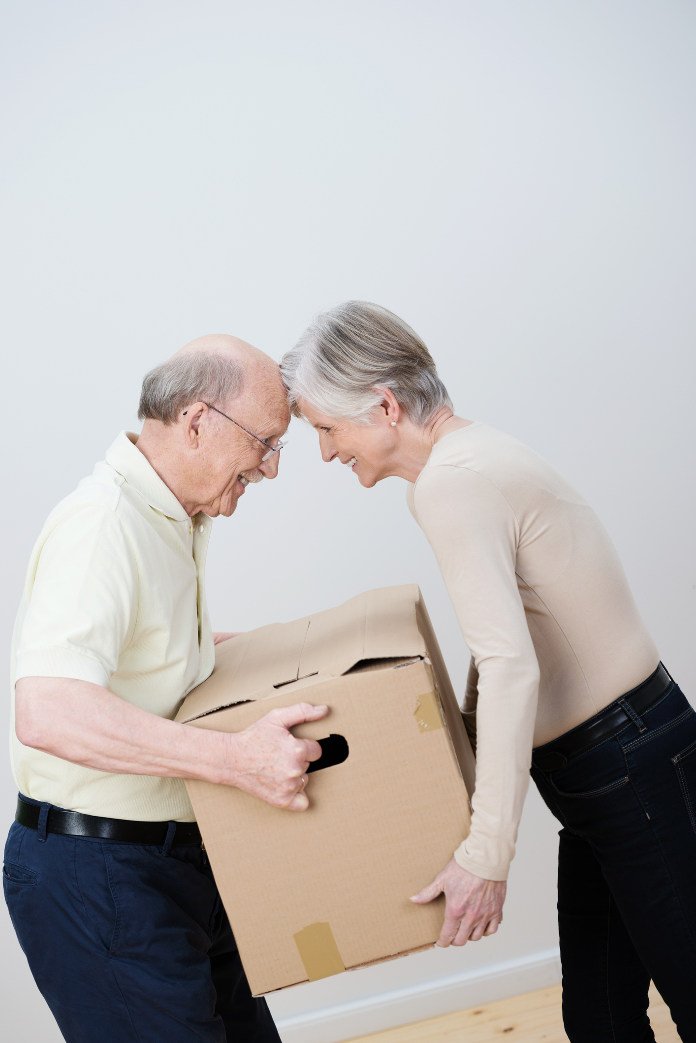 two senior citizens carry a moving box together