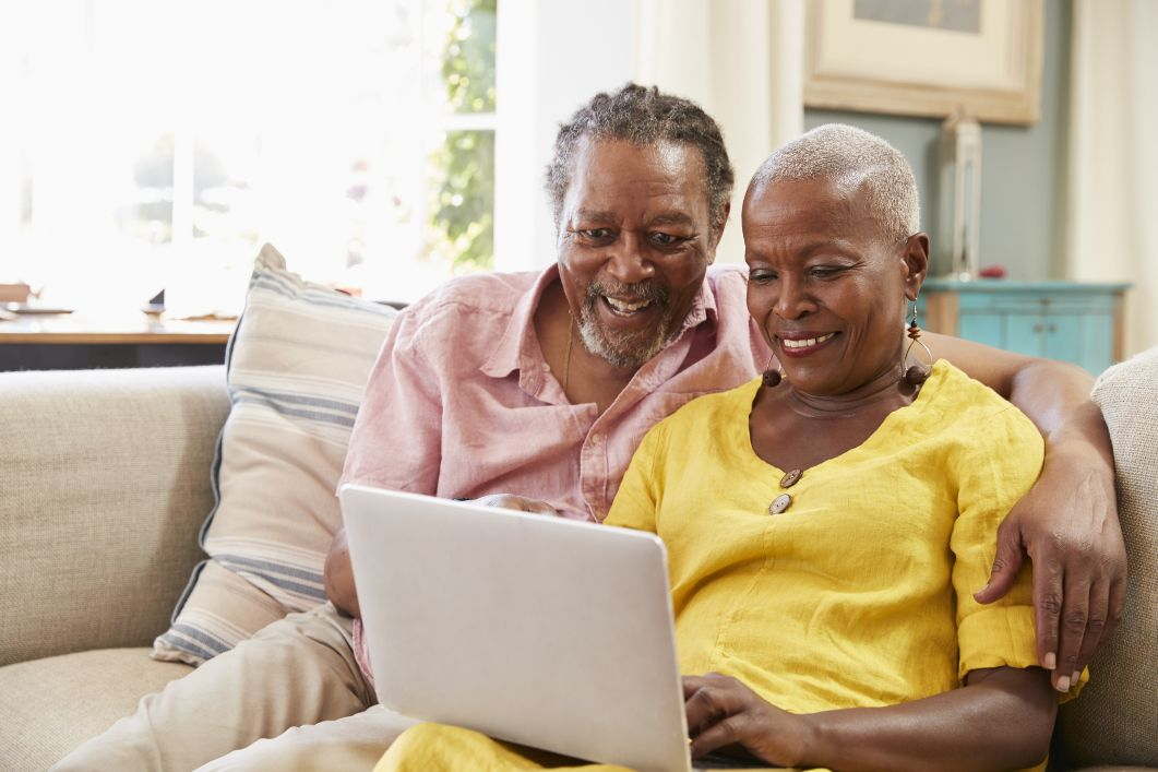 an elderly man has his arm lovingly over an elderly woman's shoulder while they both smile at a computer screen while selling an inherited house
