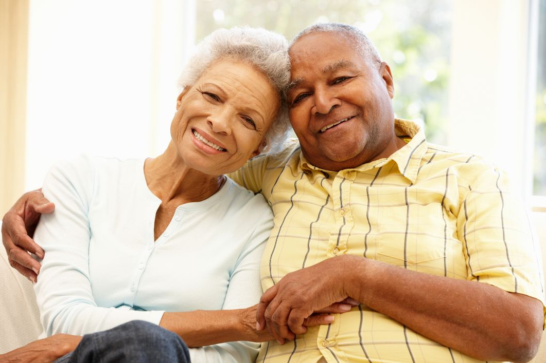 an elderly couple smiling at the camera while holding hands