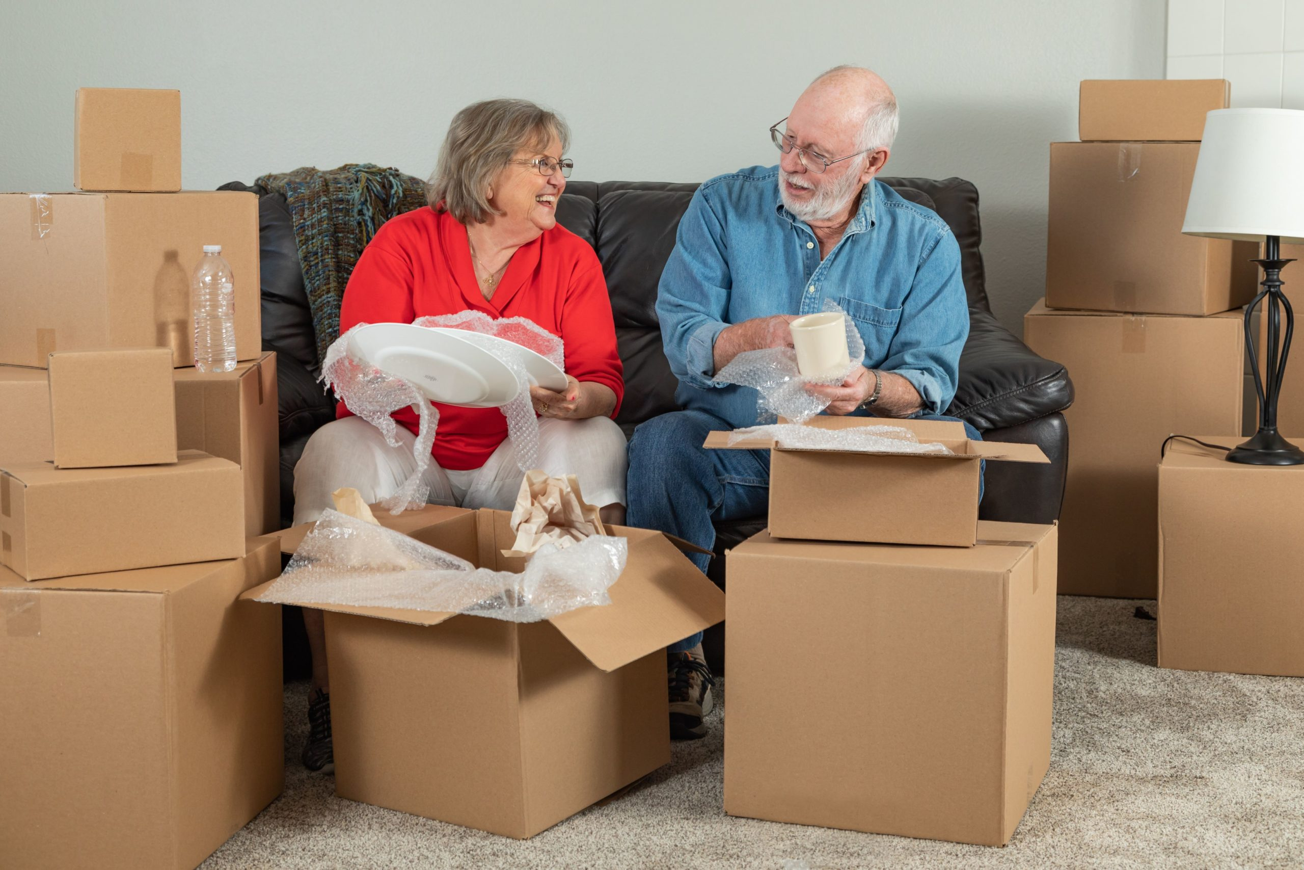 senior adult couple downsizing home by packing boxes