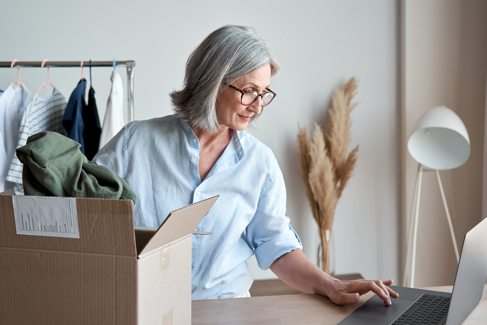 woman checking computer while packing a box